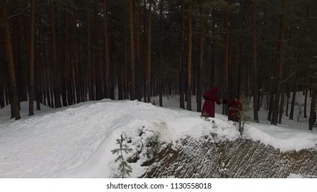 Torchlight procession. Group of monks in hood robe walking along winter snow trail in forest. Footage. Group of monks in hood robe walking along winter snow trail in forest