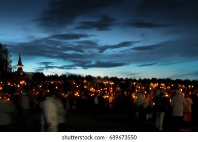 Torchlight procession. Horizontally. Night shooting. A lot of warm lights from candles, blurred shapes of people against the background of the night sky.