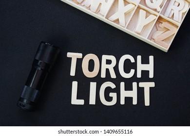 torchlight word using wooden alphabet on black background