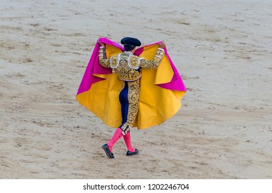 Torero inblue and gold suit and wearing montera raising his capote with his hands over shoulders in a typical spanish bullfight
