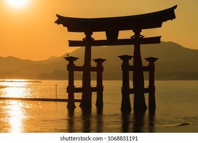 Tori gate of Itsukushima Shrine on Miyajima Island at sunset, Hiroshima, Japan