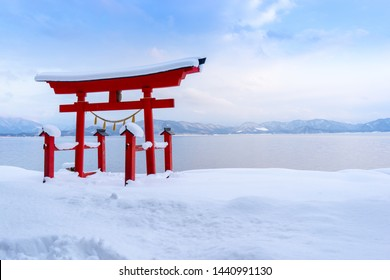 Torii gate of Goza no Ishi Shrine on snow, out over the Lake Tazawa and mountains background, Semboku, Akita Japan