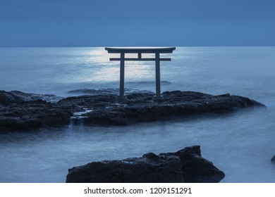 A torii standing on a rock in the sea