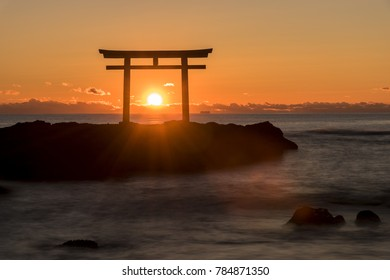 a torii that standing on the rocks in the pacific ocean