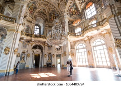 Torino, Italy - April 25 2018: tourists marvel at the grand interiors of main hall of UNESCO World Heritage Palazzina di Caccia of Stupinigi, Savoy royal hunting lodge designed by architect Juvarra