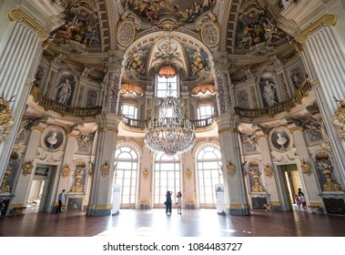 Torino, Italy - April 25 2018: tourists marvel at the grand interiors of main hall of UNESCO World Heritage Palazzina di Caccia of Stupinigi, Savoy royal hunting lodge designed by architect Juvarra