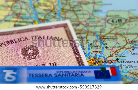 TORINO, ITALY, CIRCA DECEMBER 2016: Italian identity card and national sanitary assurance card with Uk map on the background. Many Italians live and work in London. Tilt-shift effect applied.
