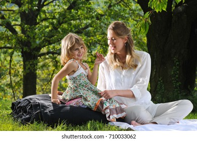 TORINO, ITALY - May 2016: Mother and daughter at a picnic outside on the grass.