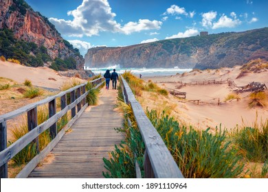 Torists walking to Cala Domestica beach on wooden pier. Windy summer scene of Sardinia, Italy, Europe. Footbridge in Canyon di Cala Domestica. Beautiful marine scenery.