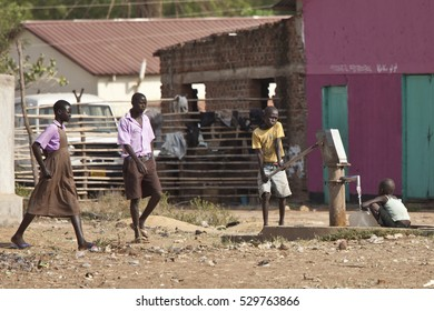 TORIT, SOUTH SUDAN-FEBRUARY 20, 2013: Unidentified children pump water from a well in South Sudan while students walk by