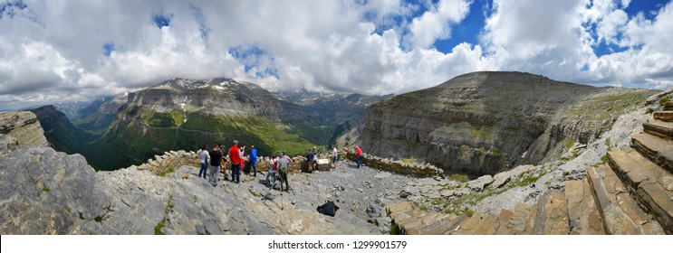 Torla, Ordesa, Spain, 6/20/2018 Panorama of a group of people standing at a high viewpoint watching canyons mountains and valleys of the Ordesa national park in the Pyrenees in Spain on a sunny day