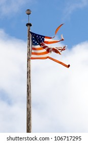 Torn American flag flying from a rusty pole.  Shot against a blue sky with clouds.