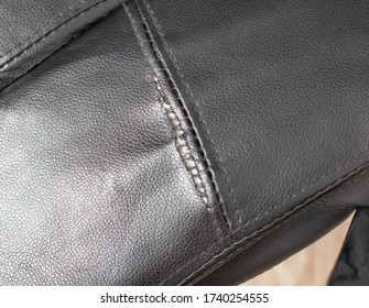 Torn and battered leather on a black office computer chair. Restoration and restoration of the leather, copy space