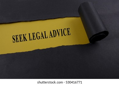 """Torn black paper on yellow surface with """"SEEK LEGAL ACTION"""" word. Business concept"""
