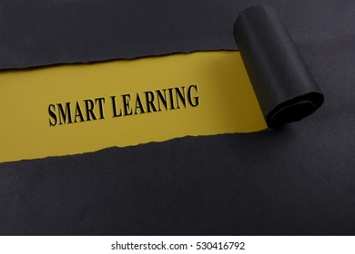 """Torn black paper on yellow surface with """"SMART LEARNING"""" word. Business concept"""