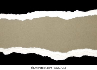 Torn black and white paper on brown background. Copy space