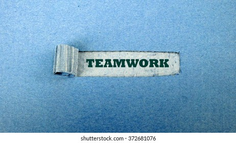 "Torn blue paper on dull blue surface with ""teamwork"""