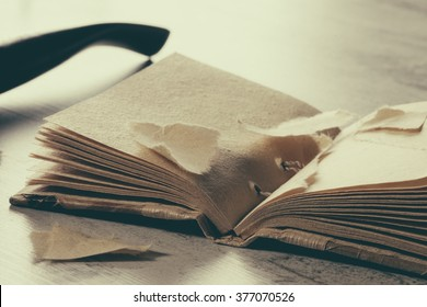 Torn book with empty pages in hardcover on table