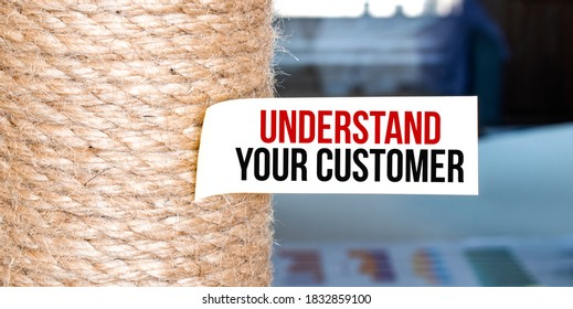 Torn brown paper on white surface with text UNDERSTAND YOUR CUSTOMER