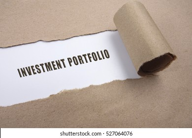 """Torn brown paper on white surface with """"investment portfolio"""" word. Business concept"""