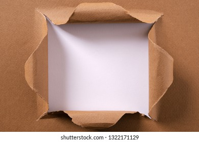 Torn brown paper square hole background frame