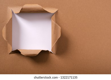 Torn brown paper square hole white background frame