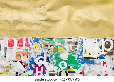 Torn, crumpled and scratched golden glossy paper placard on dirty billboard with old ripped and peeling pieces of paper posters background. Copy space for text.