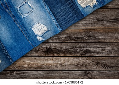 Torn Denim jeans pants collection. Many ripped blue trousers on wooden background. Trendy fashion design, top view, copy space