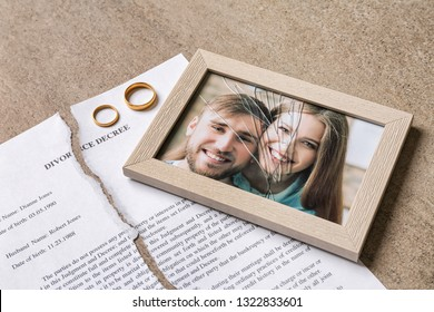 Torn divorce decree, rings and broken frame with photo on table