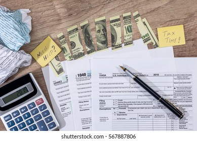 torn dollars on tax form, pen and calculator.