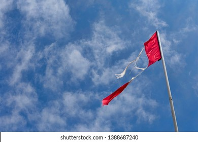 Torn flag fluttering in the wind on flagpole under clouds with blue sky