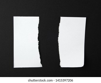 torn in half empty white sheet of paper on black background, close up