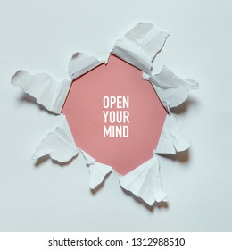 Torn hole in the white paper with text Open Your Mind. Concept of seeing the world, traveling, open your mind, creativity
