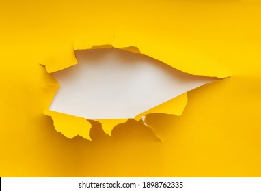 Torn hole in yellow paper with a white background. Concept for placing text or other elements, copy space, mockup.