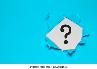 Torn out blue paper with question mark symbol
