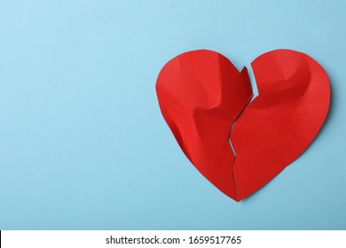 Torn paper heart on light blue background, top view with space for text. Relationship problems concept