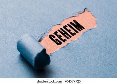"torn paper revealing the word ""secret"" in German"