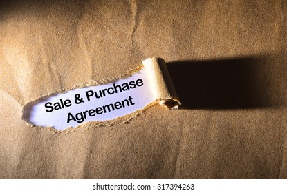 torn paper with word Sale And Purchase Agreement