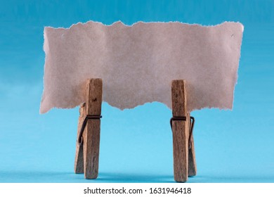 Torn piece of blank white paper on wooden clothespins.
