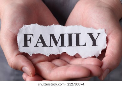 "Torn piece of paper with the word ""Family"" in the woman's palms. Close-up."