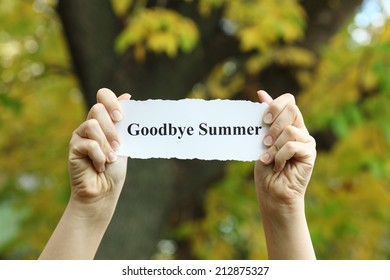 """Torn piece of paper with the words saying """"Goodbye Summer"""" in the woman's hands against autumn background."""