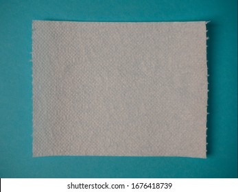 Torn sheet of toilet paper on a blue background close up with copy space.