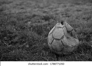 Torn soccer ball lies on the old grass. BW photo