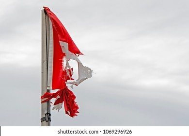 A torn and tattered red and white flag hangs from a flagpole. Much of the flag is missing. Overcast sky.