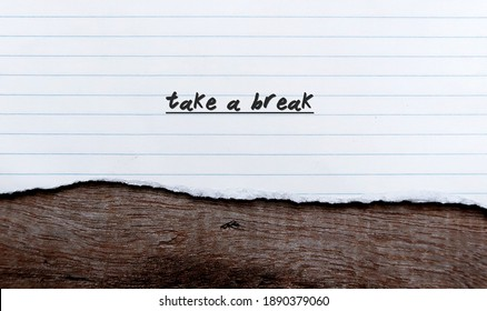 Torn white old style note sheet paper on wood background with handwritten text TAKE A BREAK, concept of self reminder to relax, stress free , stay out of conflict