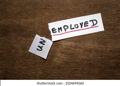 Torn, white paper sheet with inscription unemployed on the brown wooden office desk. Unemployment status is over. Found new job. Hiring concept.