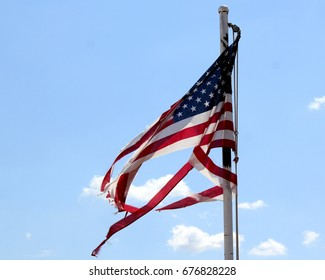 Torn worn tattered distressed red white and blue United States American flag flapping in the wind against a blue Arizona sky. Old Glory.