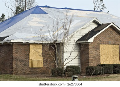 tornado aftermath of a damaged brick house with the windows boarded and the roof has a tarpaulin covering it.