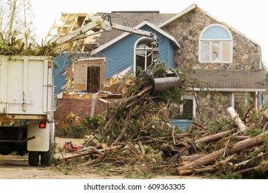 Tornado damaged house with tree removal truck equipment removing fallen trees.
