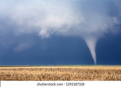 Tornado over a field with dark storm clouds.